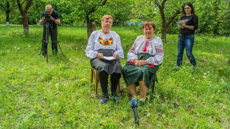 Two Ukrainian women dressed in traditional clothing sit on chairs in a green field. There is a camera crew behind them.