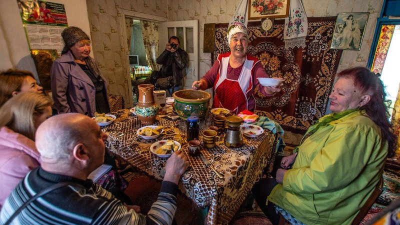 A group of Ukrainians sit around a table filled with food. They are in a colorful room.