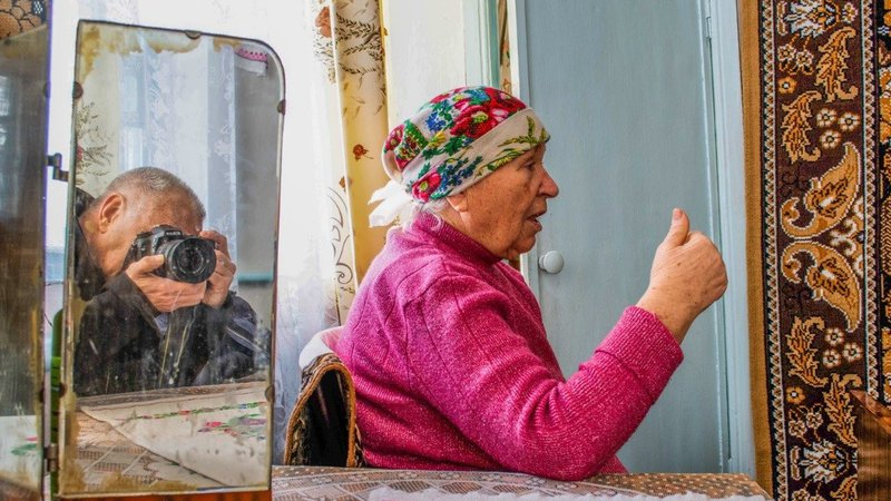 A woman sits amid an ornately decorated room, telling a story. Michael is reflected in a mirror taking her photo.