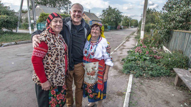 A white American male stands with his Ukrainian friends outside on a road