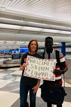 """A female Returned Peace Corps Volunteer stands in an airport with her Ghanaian friend holding a """"welcome Stephan"""" sign."""