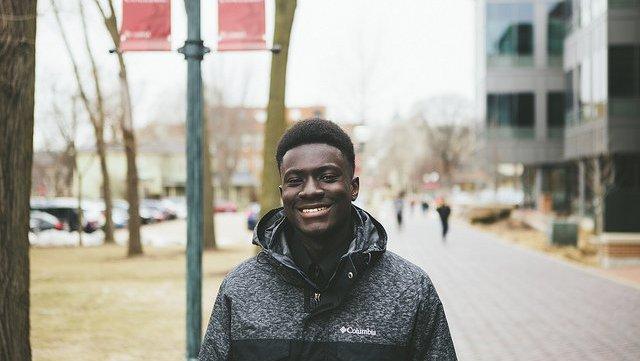 A Ghanaian twenty-something male smiles outside on a city street.