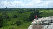 A woman sits on a rock overlooking a green landscape in Cameroon