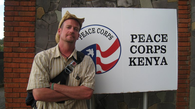 A young, white man wearing a cowboy hat stands outside in front of a Peace Corps Kenya sign.