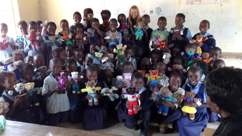 A Peace Corps Zambia Volunteer and her second grade class pose for a photo.
