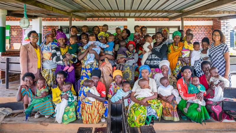 Group photo of mothers with babies, PCV Maya, and counterpart Gaudence