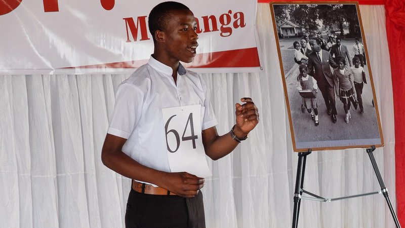 A student delivers a speech from the front stage