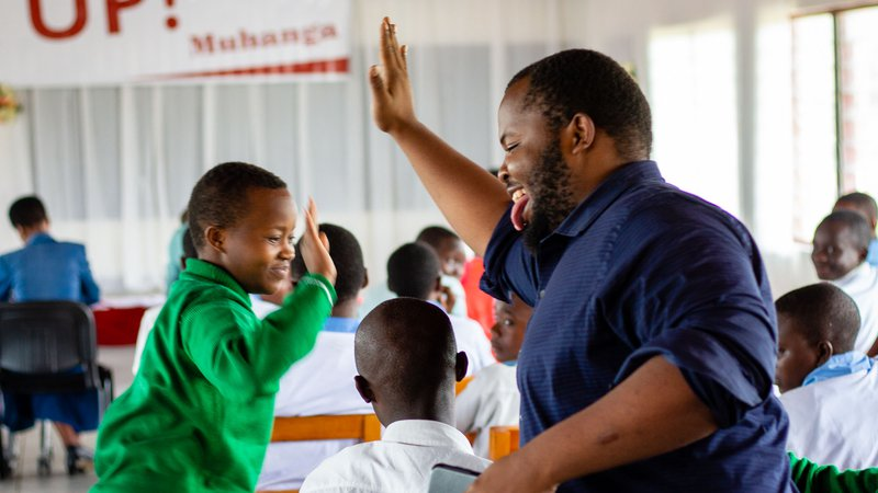 PCV Moses gives a high-five to a student