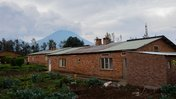 A rural Rwanda house in the foreground and a volcano in the background
