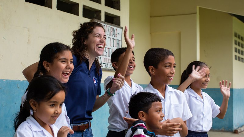 Woman in blue shirt surrounded by school children from Panama