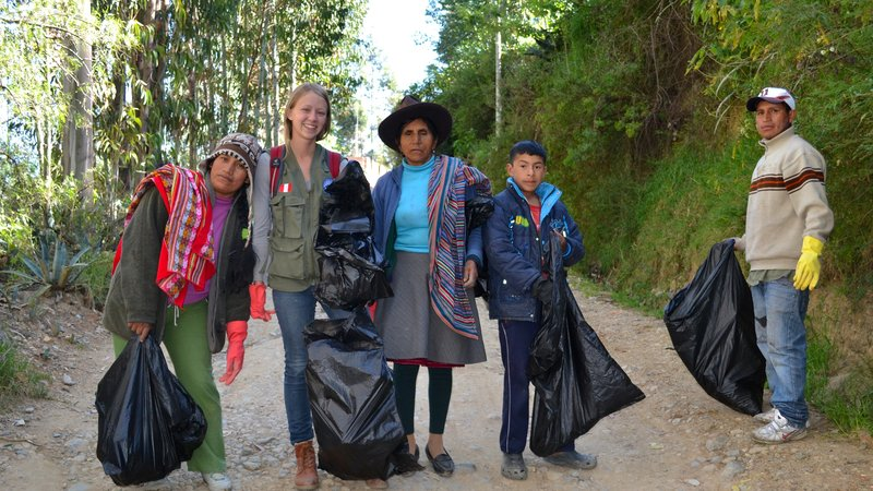 A Volunteer and commmunity members hold bags of trash collected during a community clean up.