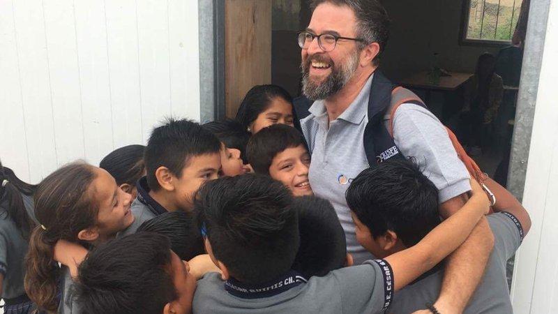 Volunteer Lobo is encased in a group hug by the children he helps teach.