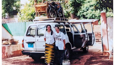 Two female Peace Corps Volunteers stand behind a packed truck.