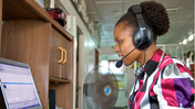 Professionally dressed young black woman works on computer while wearing a headset