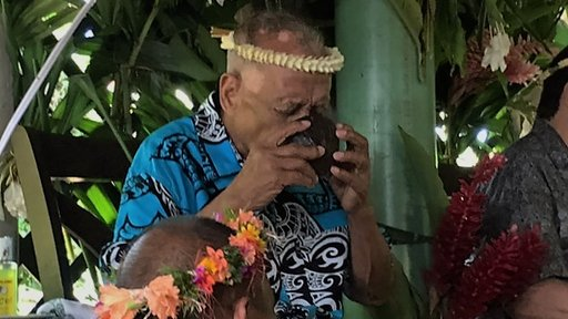 Taking sakau from a traditional half coconut shell