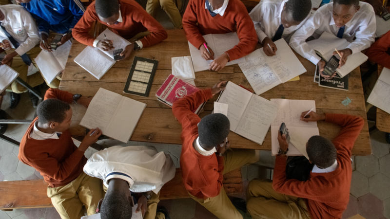 An overhead shot of a classroom in Tanzania. Students are wearing red sweaters.