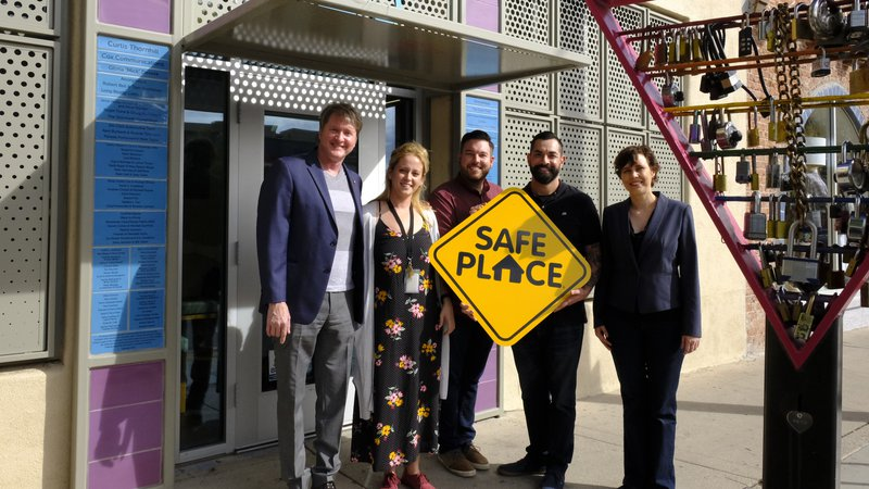 "Five coworkers pose for a picture outside of their office building. They are holding a yellow sign that says ""Safe Place"""