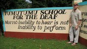 A young, white man stands outside next to the gate of TumuTumu School for the Deaf in Kenya..
