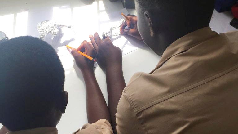 Two Jamaican students sitting down at a table constructing a sculpture made out of foil and drawing out the design