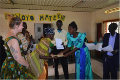 A homestay mother receives her certificate from the guest of honor as excited Lauren looks on
