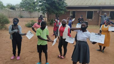 Youth in school uniforms proudly hold their GRS completion certificates
