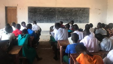 Students sit at desks looking at the blackboard in a classroom