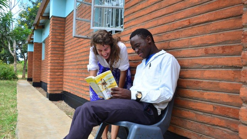 A female Volunteer works with a male student outside, with the help of a yellow book.