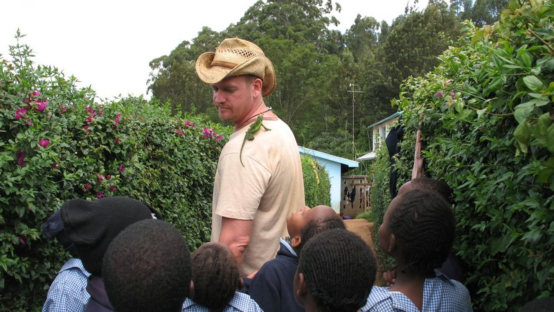 A young, white man shows off a chameleon on his shoulder to a group of young Kenyan students