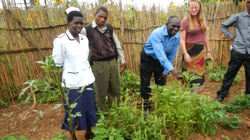 Health center workers show other community members their permagarden.