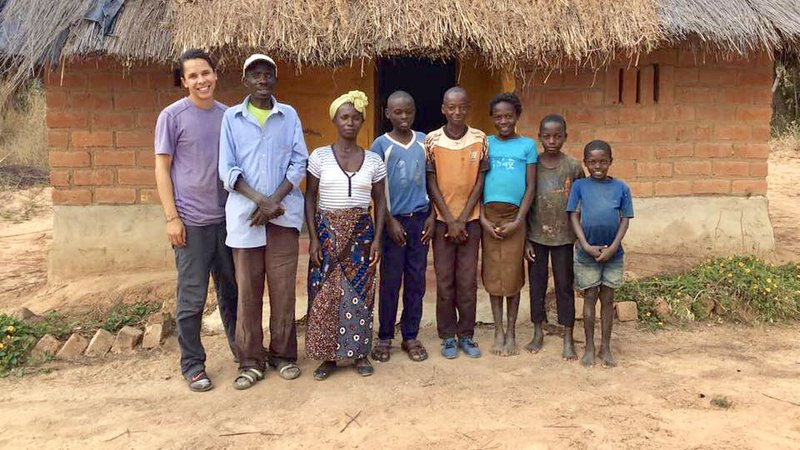 A Peace Corps Volunteer stands with his Zambian host family outside their home.
