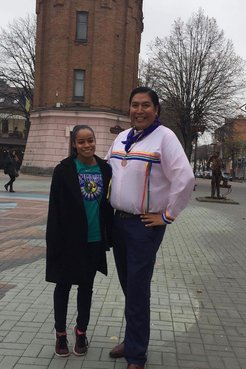 Two people of Indigenous heritage stand outside in their traditional clothing.