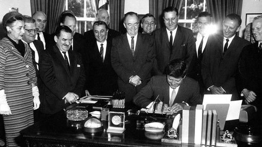 President Kennedy signing the Peace Corps Act as Hubert Humphrey (center) looks on. (Abbie Rowe, National Park Service)