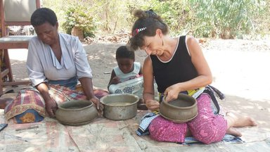 Birgit sits on a bamboo mat with a Malawian woman and a child as they hold and mold clay pots in their laps