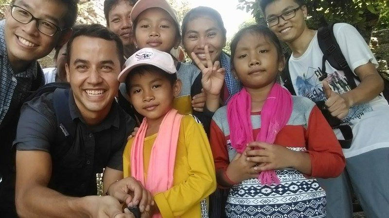Latinx Volunteer poses with his Cambodian host family.