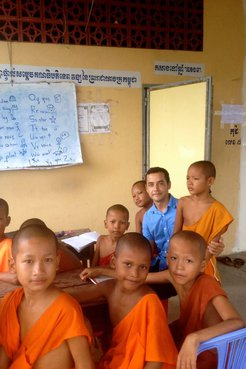 Latinx Volunteer teaches young Cambodian monks in his community.