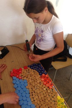 Making a mural with bottle caps.