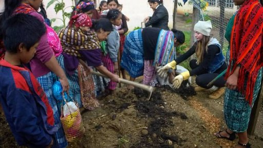 Peace Corps Volunteer Nicole Mortenson plants a demonstrative garden with mothers.