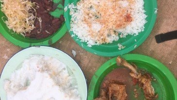 Traditional Malawian food sits in green plates on a beige mat. The food is chicken, nsima, beans, and cabbage.