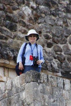 Carolyn standing near the top of a Mayan pyramid at Uxmal enjoying views of Green Jays and an Altamira Oriole.