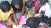Little girls read in Malawi with the help of their teacher