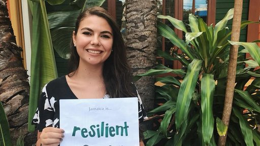 """Turkish Female Peace Corps Volunteer holds a sign that reads """"Jamaica is Resilient"""" in front of an orange building."""
