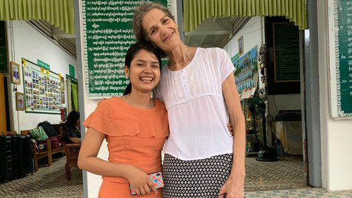 A tall, middle aged white woman and a young, short woman from Myanmar stand side by side, smiling and embracing..