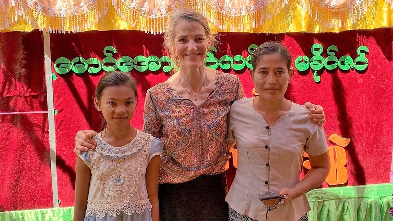 Two young women from Myanmar stand on either side of an older white woman, who is smiling.