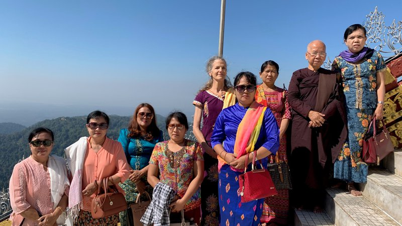 A large group of people in colorful, traditional Myanmar dress stand outside on a cliff.