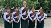 Five middle aged women stand in a row, outside, in traditional Burmese green and white outfits.