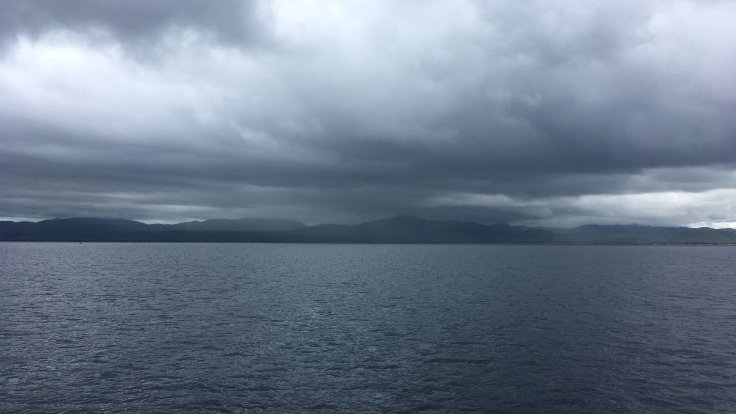 Storm clouds accumulate over a grey Lake Malawi