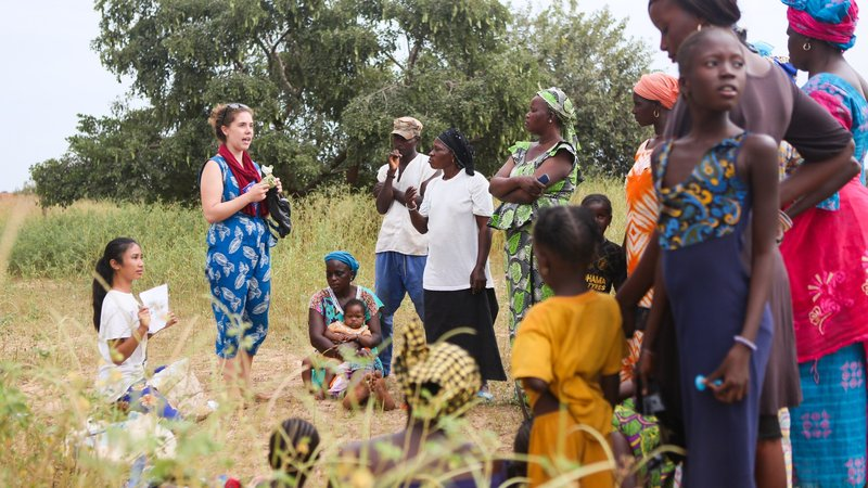A American female volunteer stands in a field with many Senegalese individuals.