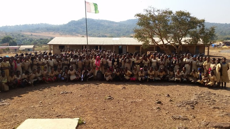Students posing in front of school