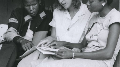 A Volunteer sits with two of her students in Botswana.