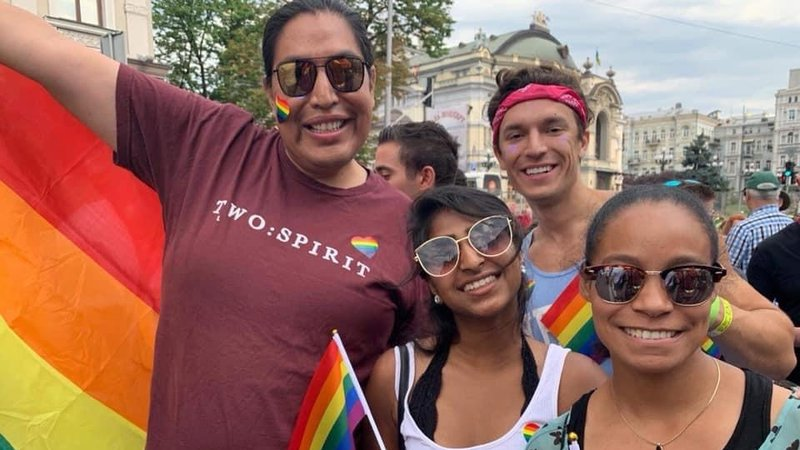 A group of friends huddle together for a picture, smiling, while waving rainbow Pride flags.